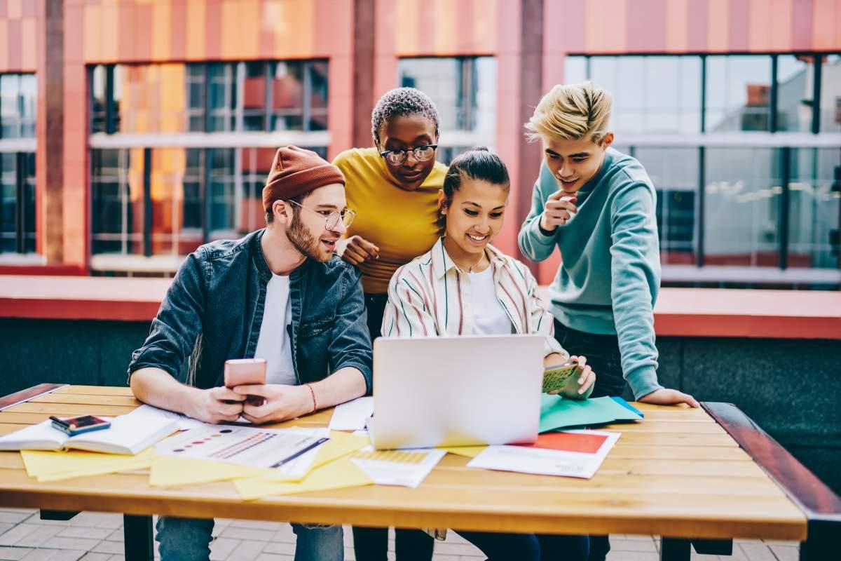 Gruppe von vier Millennials arbeiten an einem Tisch im Freien und schauen auf einen Smartphone-Screen