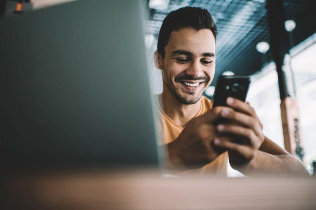 Junger Mann blickt auf ein Smartphone und lächelt, im verschwommenen Vordergrund ein Laptop-Screen