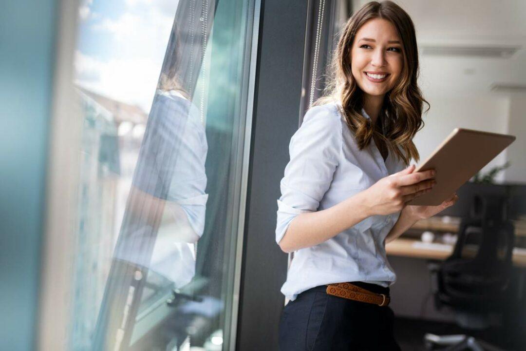Junge Business-Frau steht am Fenster im Büro mit Tablet in der Hand, sie blickt nach draußen und lächelt