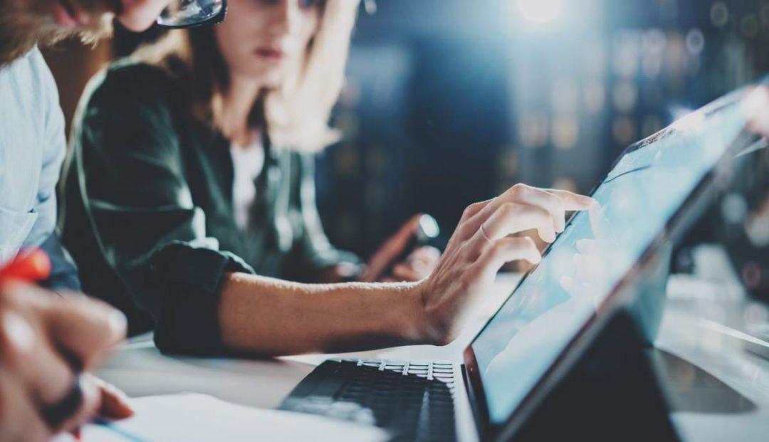 Eine Frau deutet auf Daten auf einem Laptop-Screen, ein Mann macht handschriftliche Notizen