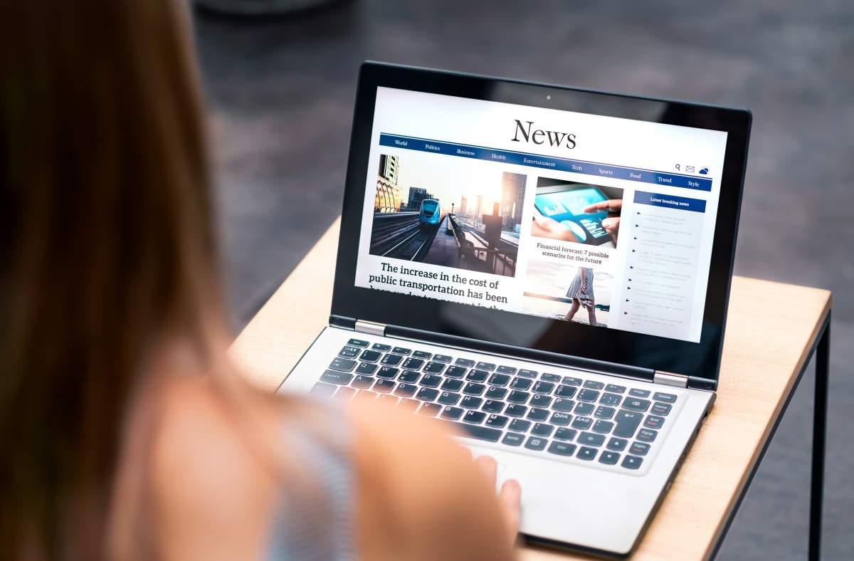 Blick über die Schulter einer Frau, die die Schlagzeilen und Überschriften auf einer News-Seite auf dem Laptop ansieht